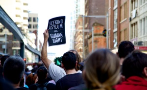 "Protester holding sign sayin ""seeking asylum is a human right"""